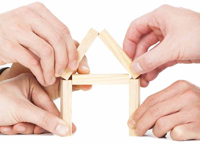 Hands building a house out of blocks.